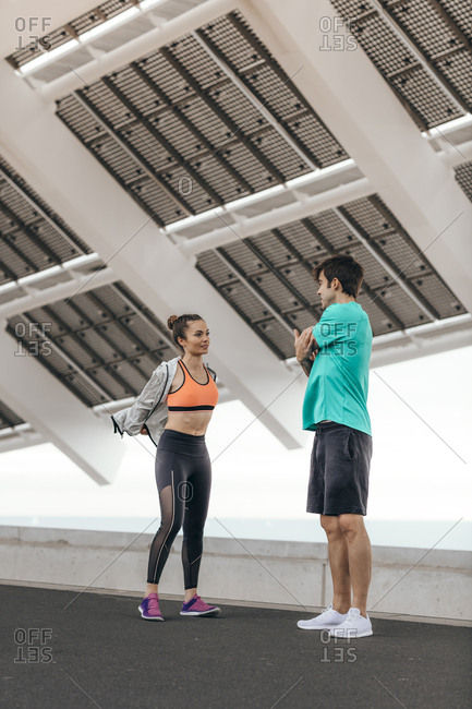 Young man and woman stretching before a run