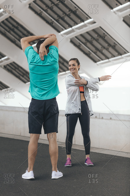 Young woman and man stretching before a run