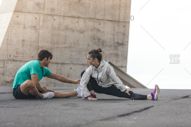 Young couple stretching their legs before a run