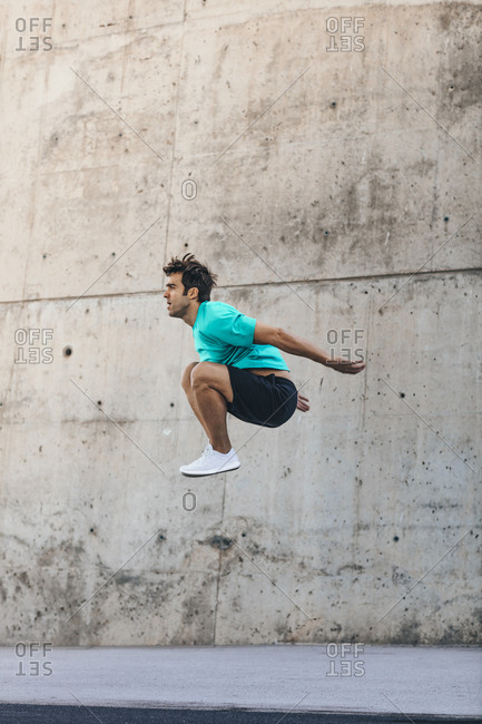 Man jumping high in the air during workout