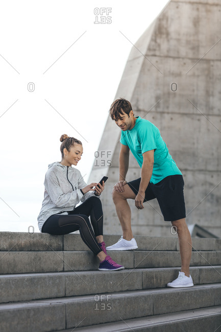 Couple resting during workout and looking at phone