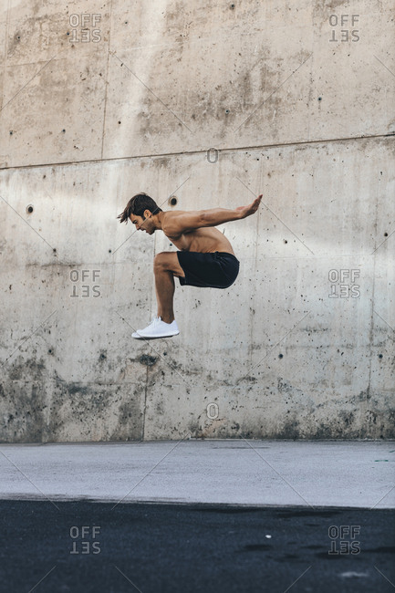 Shirtless man jumping high in the air during workout
