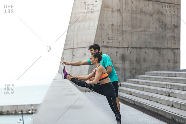 Young couple stretching legs on waterfront steps