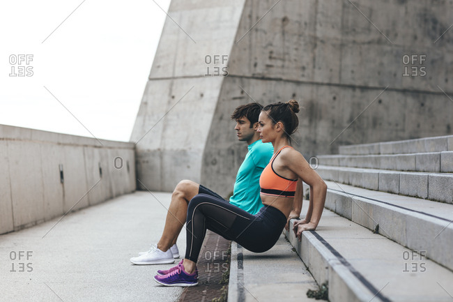 Young couple working out on concrete steps