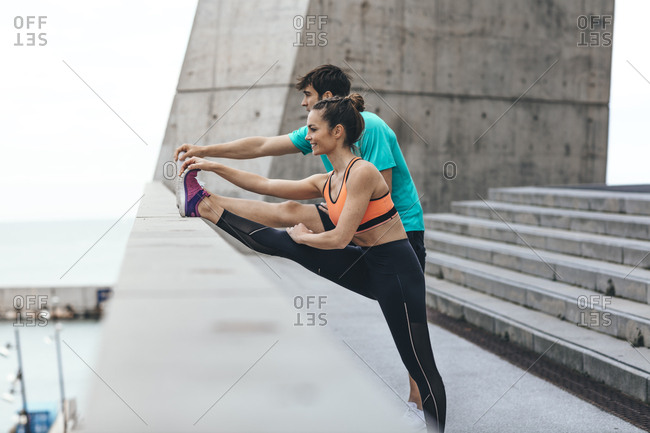 Happy young couple stretching legs on waterfront steps