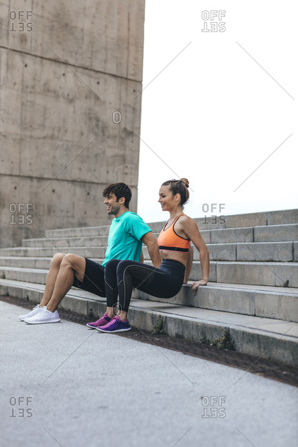 Happy young couple doing dips on concrete steps