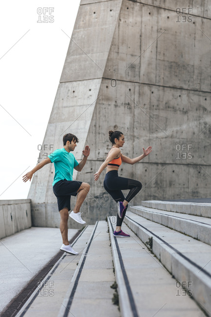 Couple working out on concrete steps