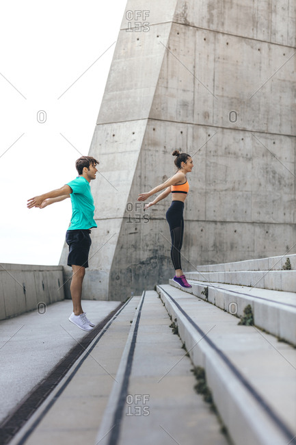 Couple jumping up concrete steps during workout