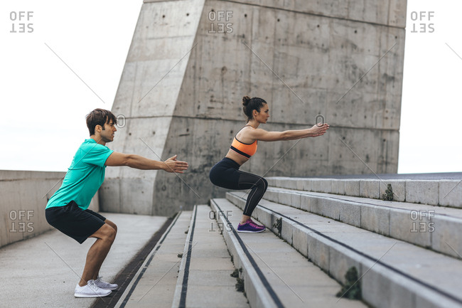 Couple doing squats on concrete steps during workout