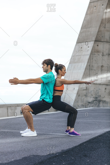Couple doing back to back chair squats during workout
