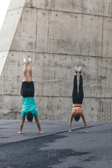 Rear view of couple doing handstands during urban workout