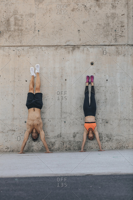Couple doing handstands during urban workout