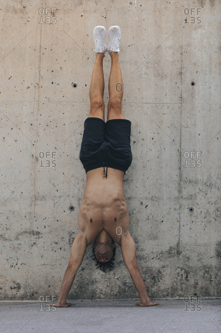 Shirtless man doing handstand on concrete wall
