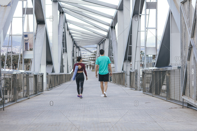 Rear view of couple walking on bridge after workout