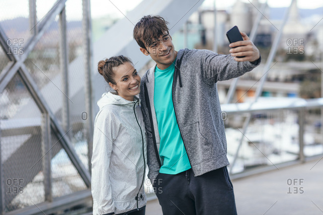 Couple in athletic clothing posing for selfie on a bridge