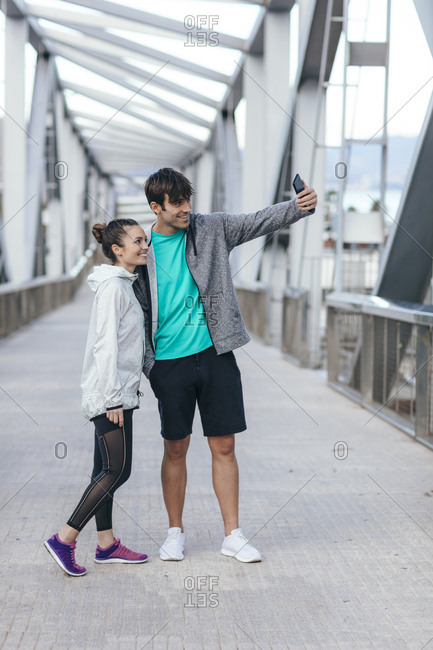 Couple in athletic clothing taking a selfie on a bridge