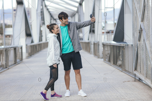 Young couple in athletic clothing taking a selfie on a bridge
