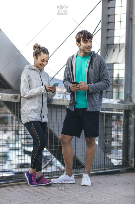 Young couple in athletic clothing standing on bridge using cell phones