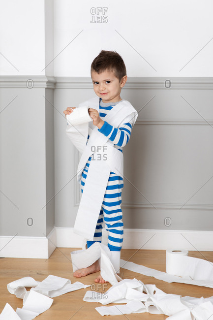 Young boy wrapping toilet paper around himself
