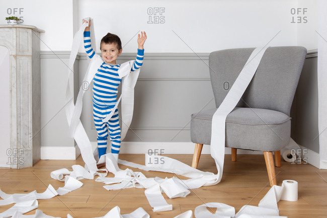 Young boy making a mess with rolls of toilet paper