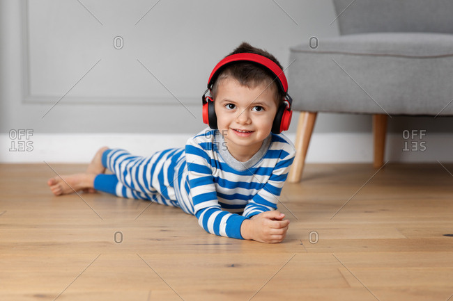 Little boy lying on floor wearing red headphones