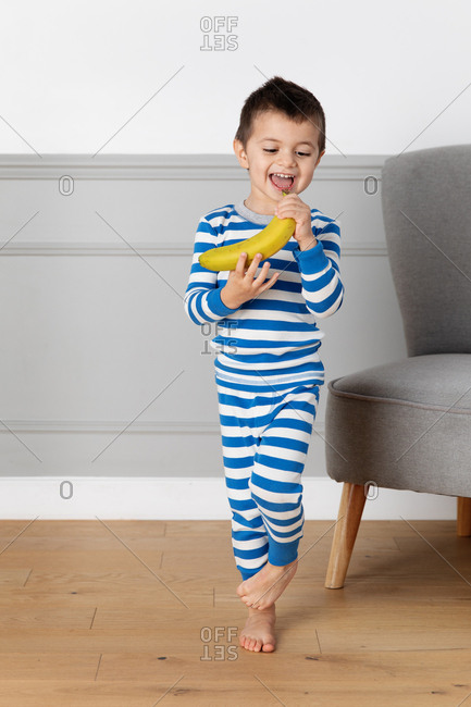 Little boy singing into a banana
