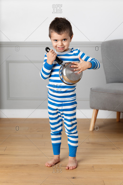 Little boy playing with pot as an instrument