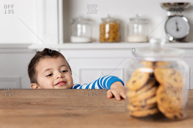 Young boy reaching for cookie jar
