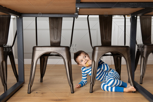 Young boy sitting under kitchen table eating a cookie