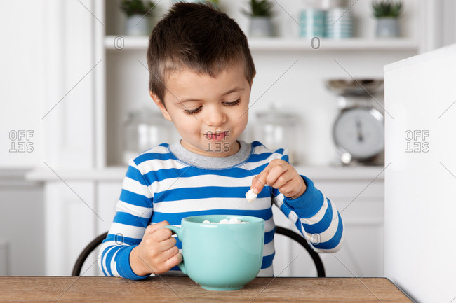 Little boy picking a marshmallow from his cup of hot cocoa
