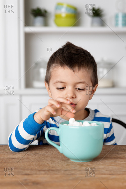 Little boy picking a marshmallow from his hot cocoa