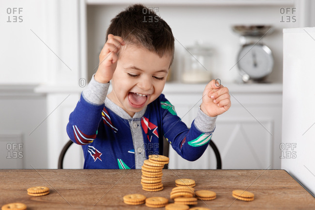 Little boy making a stack of cookies