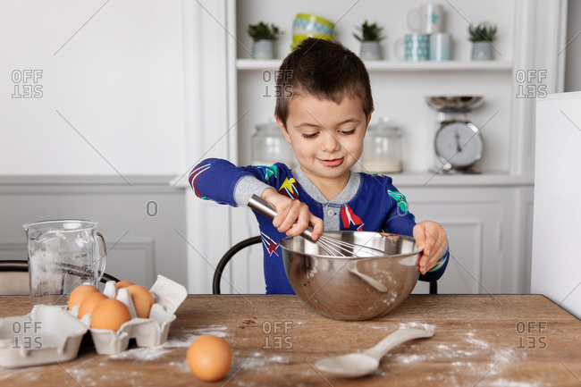 Little boy mixing a dessert in a bowl