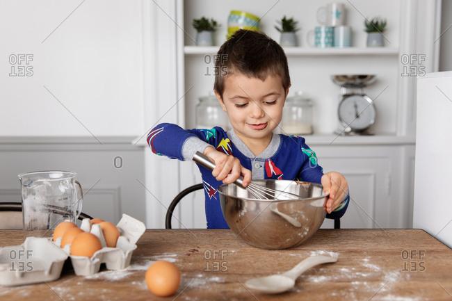 Little boy mixing a dessert in a bowl