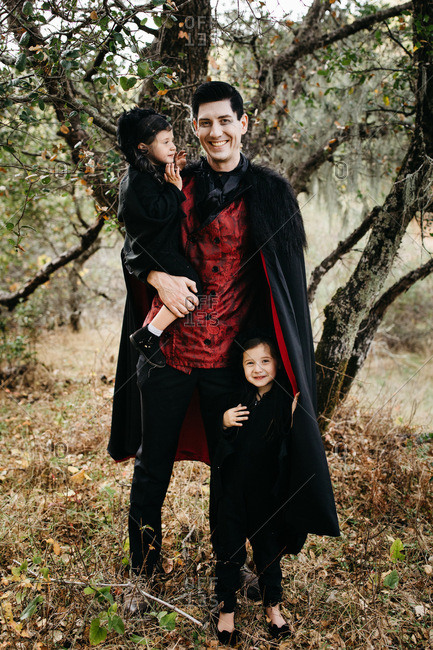 Young girls wearing a bat Halloween costume and father as a vampire