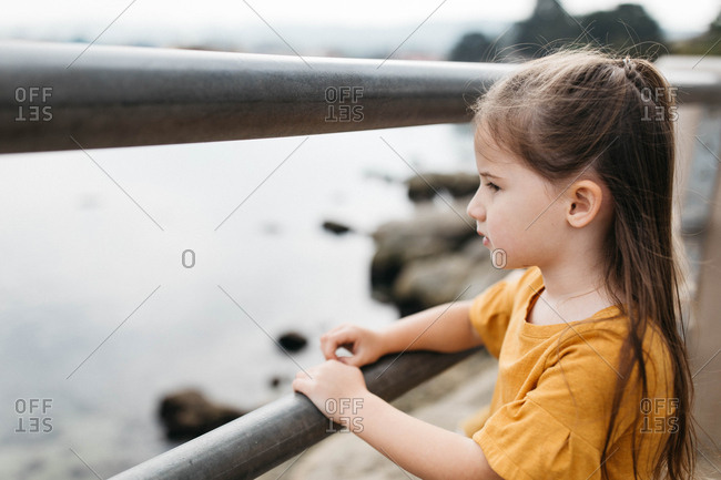 Little girl looking through railing out at ocean