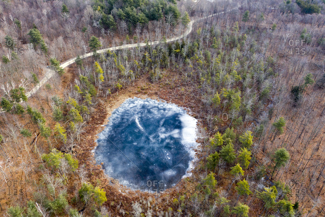Drone view of a small round Mud Pond and country road through a forest in winter in Sudbury, Vermont.