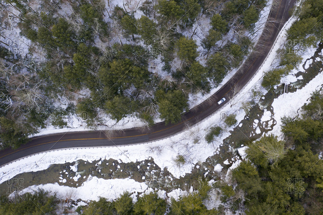 Drone view of car driving in winter along Route 125 and the Middlebury River in Ripton, Vermont.