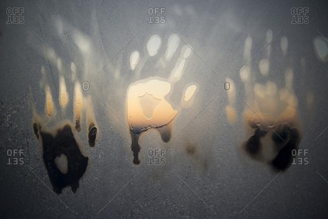 Child's hand prints on window in winter in Brandon, Vermont.