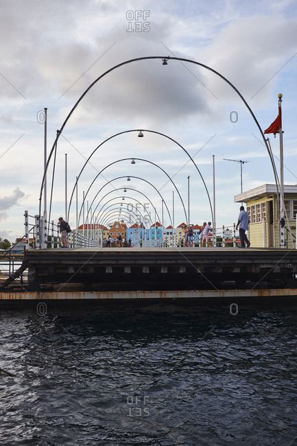 Willemstad, Curacao - October 31, 2018: The floating boat bridge opens up. Part of the historic and colorful waterfront buildings of Willemstad. The Dutch architecture has UNESCO World Heritage Site status.