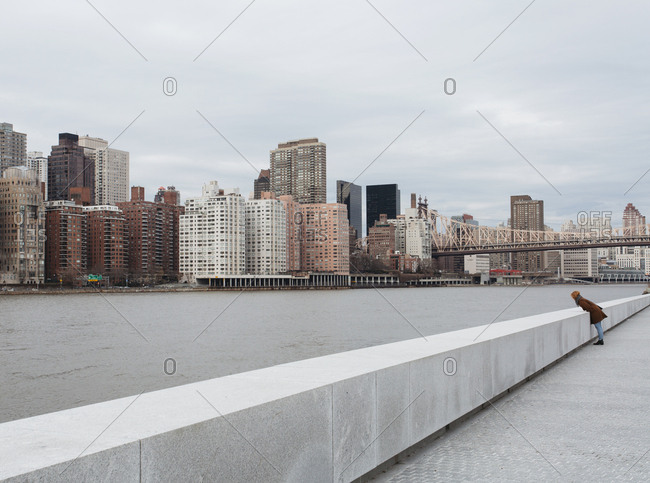 Redhead woman looking at east river and Manhattan skyline