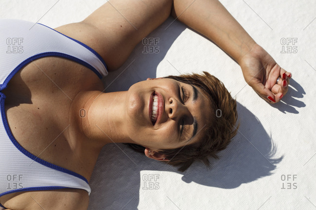 Portrait of laughing young woman taking sunbath