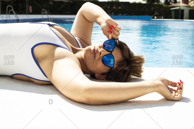 Portrait of plump young woman taking sunbath at swimming pool