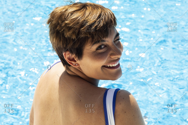 Portrait of winking young woman at swimming pool