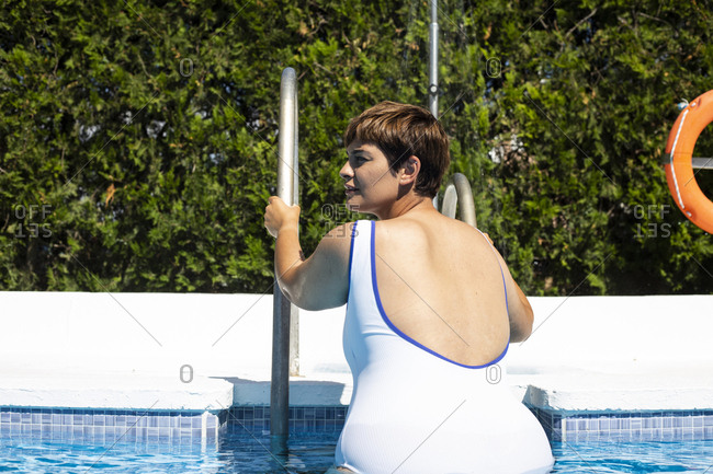 Back view of plump young woman leaving swimming pool