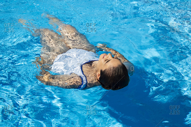 Young woman floating on water in swimming pool