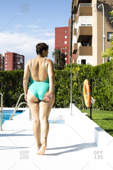 Back view of plump young woman walking next to swimming pool
