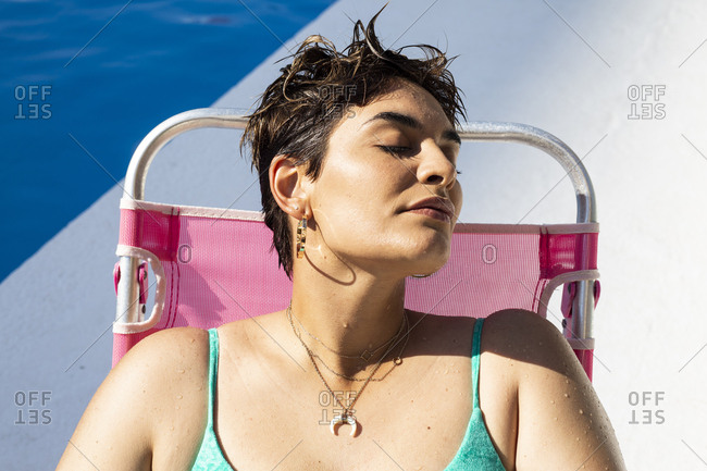 Portrait of young woman relaxing on sun lounger at swimming pool