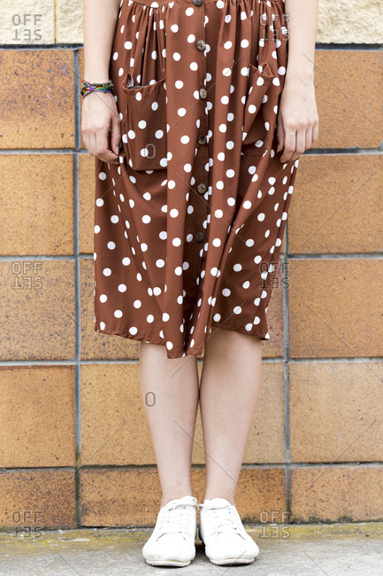 Young woman wearing brown dress with white polka dots- partial view