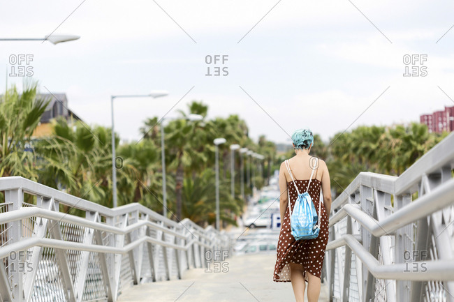 Spain- back view of young woman with blue dyed hair with backpack walking on a bridge